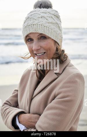 Spanien, Menorca, Portrait von lächelnden älteren Frau bobble Hut auf dem Strand im Winter - Stockfoto