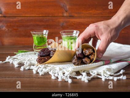 Iftar oder suhoor Snack, einen Mann mit einem Konus von Datumsangaben mit mentha Tee auf Hintergrund, Ramadan Konzept - Stockfoto