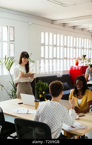 Lächelnde Frau mit Zwischenablage unter Kollegen im Büro - Stockfoto