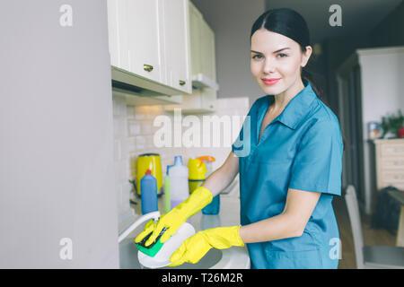 Horizontale Portrait von Mädchen wäscht Geschirr in der Spüle. Sie ist in der Küche. Brunette lächelt und sieht auf der Kamera. Sie trägt eine blaue Uniform und gelbe Handschuhe - Stockfoto