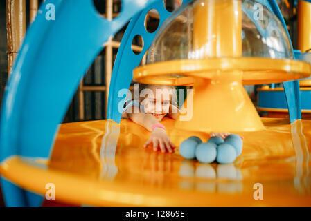 Funny Girl spielt mit Kugeln auf Air Maschine, Kinder Game Center. Aufgeregt haben Kinder Spaß auf dem Spielplatz im Freien. Weibliche Kid spielen in Amusement cent - Stockfoto