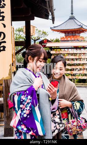 Zwei Frauen in traditioneller Kleidung, Smartphone suchen, lächelnd, Kiyomizu-dera Tempel, Kyoto, Japan - Stockfoto