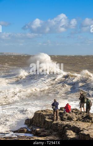 PORTHCAWL, WALES - Oktober 2018: Gruppe von Leuten auf den Felsen in Porthcawl, die Bilder von großen Wellen auf die Flut. - Stockfoto