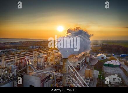 Die Produktion von Holzplatten, der Rauch von Leitungen erstellt, Verschmutzung, Burgas, Bulgarien, bei Sonnenuntergang. Erschossen von Drone. - Stockfoto