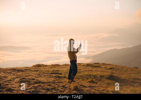 Mann in der gelben Jacke Foto auf smart phone in die Karpaten Gebirge - Stockfoto