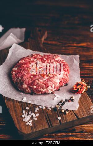 Rohes Schweinefleisch Patty mit Gewürzen auf Schneidebrett für Burger. Vertikale Ausrichtung. - Stockfoto
