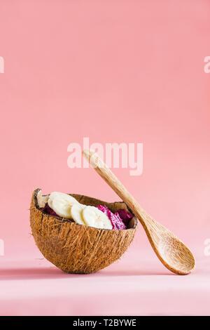 Gesund vegan Frühstück, rosa Smoothie in Coconut Teller, Schüssel aus Kokosnussschalen hergestellt - Stockfoto