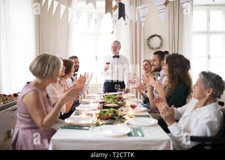 Ein großes multi Generation Familie an einem Tisch sitzen auf einem Indoor Party, ein älterer Mann, der eine Rede. - Stockfoto
