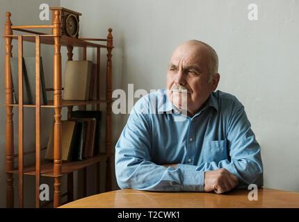 Ältere Unternehmer sitzen Denken tief seine Arme ruhen auf einem Tisch und Sie auf die Seite mit einem nachdenklichen Ausdruck - Stockfoto