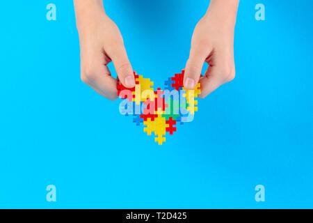 Kid hand mit bunten Herzen auf blauem Hintergrund. Welt Autismus Bewußtsein Tag Konzept - Stockfoto
