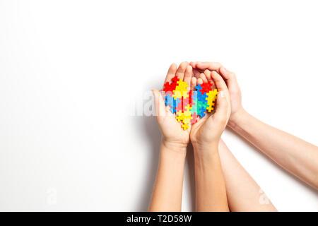 Hände halten bunte Herz auf weißem Hintergrund. Welt Autismus Bewußtsein Tag Konzept. - Stockfoto