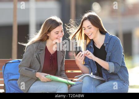 Zwei glückliche Schüler prüfen smart phone Inhalt sitzen auf einer Bank in einem Park - Stockfoto
