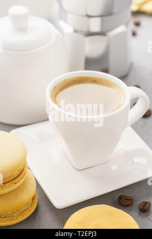 Gelbe französische Macarons mit Früchten füllen und eine Tasse Espresso. Kaffee Zeit. - Stockfoto