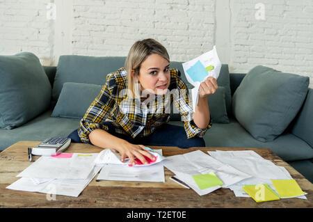 Portrait von wütender und verzweifelter Junge Frau Gefühl hervor, während sie durch Finanzen arbeiten. Auf dem Sofa sitzen, wütenden Gesten. Bei der Zahlung de - Stockfoto