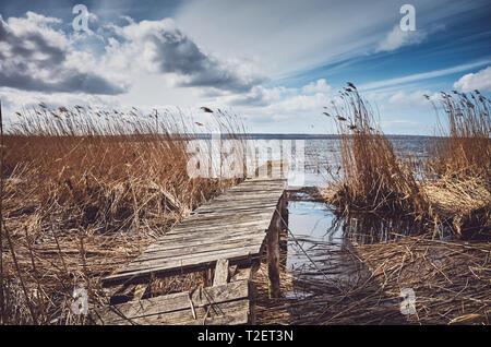 Retro getonten Bild einer alten hölzernen ramshackle Fishing Pier im Schilf, selektive konzentrieren. - Stockfoto