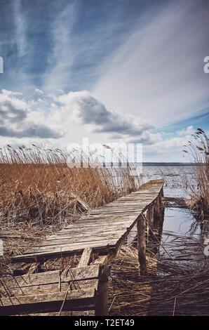 Retro getonten Bild einer alten hölzernen ramshackle Fishing Pier im Schilf. - Stockfoto