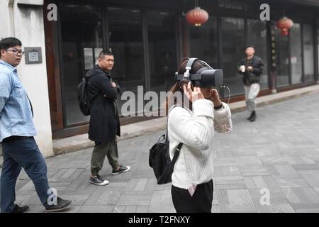 Hangzhou. 2 Apr, 2019. Eine Frau versucht, auf einem VR-Headset, das Leben von Menschen mit Autismus-Spektrum-Störungen (ASD) in Hangzhou simuliert, der ostchinesischen Provinz Zhejiang, April 2, 2019, die Welt Autismus Bewußtsein Tag. Welt Autismus Bewußtsein Tag am 2. April jedes Jahr wird bestimmt, dass die Mitgliedstaaten der Vereinten Nationen Maßnahmen zur Aufklärung über Leute mit ASD auf der ganzen Welt zu erhöhen. Credit: Huang Zongzhi/Xinhua/Alamy leben Nachrichten - Stockfoto