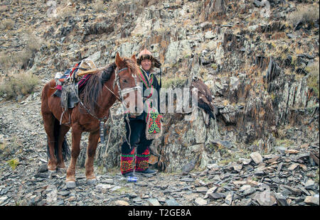Bayan Ulgii, Mongolei, 3. Oktober 2015: Kasachische eagle Jäger mit seinem Pferd und der Adler Ruhe in den Bergen - Stockfoto