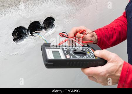 Elektriker mit Voltmeter bei der Installation von Steckdosen an der Wand im neuen Haus - Stockfoto