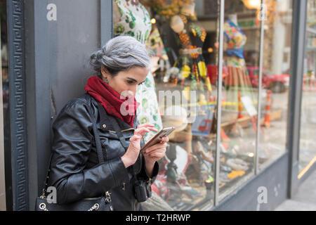 Junge grauhaarige Frau mit Handtasche und Kamera am Hals berät sich mit ihrem Mobiltelefon in Seattle, Washington, USA. - Stockfoto