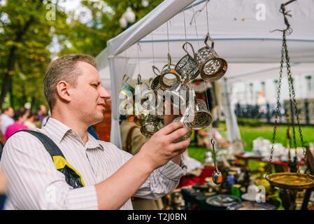 Russland, Stadt Moskau - 6. September 2014: ein Mann wählt Achterbahnen. Verkauf von Antiquitäten auf der Straße - Stockfoto