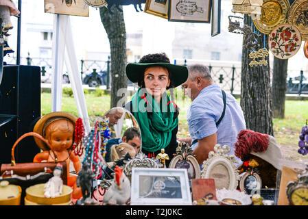 Russland, Stadt Moskau - September 6, 2014: Junge schöne Mädchen in einen Hut mit paly und grünem Schal. Eine Frau verkauft Antiquitäten in einer Straße Markt - Stockfoto