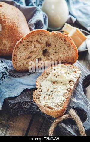 Ein schöner Laib Sauerteigbrot aus weißem Weizen auf einem Schild auf einer Leinwand. Hausgemachtes Gebäck. - Stockfoto