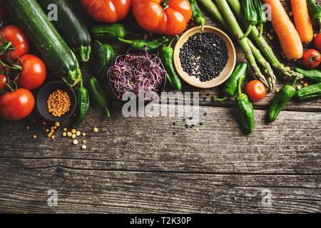 Gesundes essen Hintergrund. Sauber Essen, vegan, vegetarisch essen Konzept. Verschiedene organische Gemüse auf Holz- Hintergrund. Ansicht von oben mit Platz kopieren.