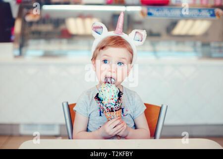 Cute adorable lustig Kaukasischen blonde Mädchen mit den blauen Augen tragen Einhorn stirnband Essen lecken Eis in große Waffel Kegel mit Streuseln.