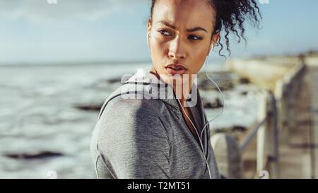 Sportliche junge Frau, die auf der Promenade und dem Strand entfernt. Läuferin Ausruhen nach einem Lauf. Stockfoto