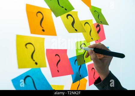 Geschäftsfrau schreiben Fragezeichen auf bunte Zettel Papier auf Office whiteboard, selektiven Fokus - Stockfoto
