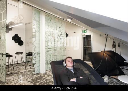 Ein junger weißer Mann entspannt Musik hören im geschäftlichen Umfeld. - Stockfoto