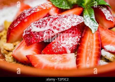 Platte mit frischen Erdbeeren und Cookie crumbles im Restaurant serviert. Selektiver Fokus - Stockfoto
