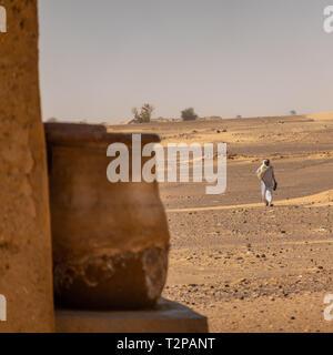 Sudan, Februar 10., 2019: Ecke von einem Lehmhaus mit einem Ton Kanne mit Wasser, Mann von der Wüste in das Haus im Hintergrund ausgeführt wird. - Stockfoto