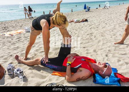 Miami Beach Florida Nautica South Beach Triathlon Atlantik Sport Fitness Sportler Konkurrenten dehnen Mann Frau paar t - Stockfoto