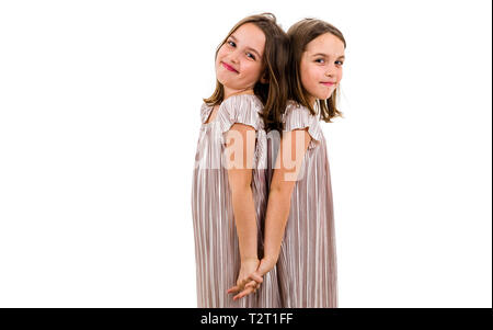 Identische Zwillinge sind, Rücken an Rücken. Konzept der Familie und schwesterliche Liebe. Profil Seitenansicht der Schwestern spielen, zu lächeln und zu lachen. - Stockfoto