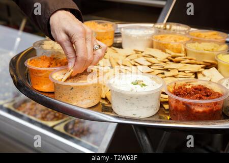 Die Hand einer Frau Geschmack verschiedene Saucen. Eine Menge Saucen in kleinen Platten für die Verkostung. - Stockfoto