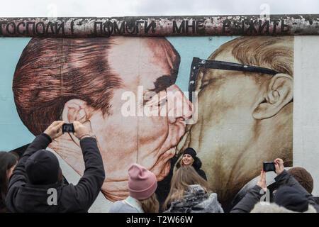 """Touristen an der 'Mein Gott, hilf mir, diese tödliche Liebe"""" (oder """"brüderliche Kuss') Wandmalerei von Dimitri Vrubel an der East Side Gallery in Berlin, um zu überleben. - Stockfoto"""