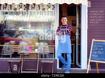 Porträt einer selbstbewussten jungen Mann in der Tür einen Coffee Shop. Tee und Kaffee Shop auf dem Fenster geschrieben. Verkehr Reflexion. Seine welcomi - Stockfoto