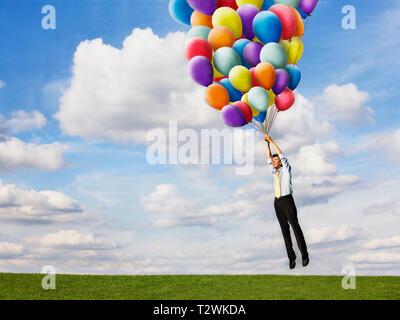 Unternehmer, die holding Helium Luftballons - Stockfoto