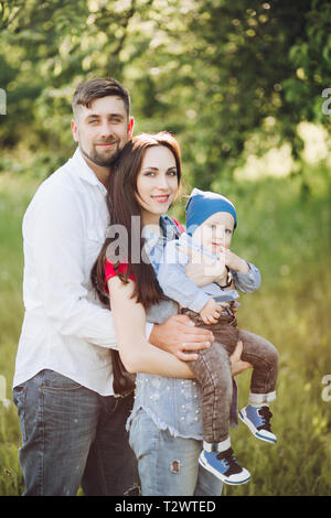 Brünett Mann küsste seine Frau, Frau mit kleinen Sohn und ihn umarmte. Seitenansicht der glücklichen Familie, tragen in Freizeitkleidung, Zeit toget - Stockfoto