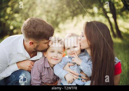 Porträt der jungen glückliche Familie, tragen im casual Outfits, Zeit miteinander zu verbringen im Park. Mann und Frau und seinem kleinen Sohn, Jungen und Smil - Stockfoto