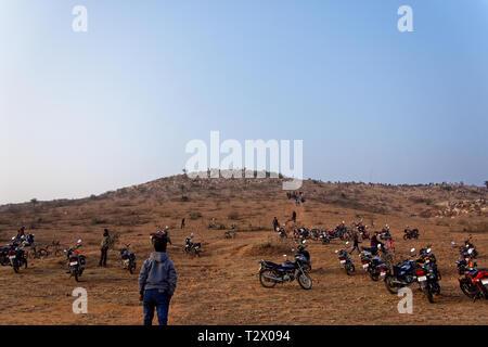 Menschen sind Klettern auf einem indischen Hügel Motorrad halten an der Unterseite - Stockfoto