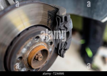 Bremsscheiben vorne mit den Bremssattel und die Bremsbeläge im Auto, auf ein Auto in eine Werkstatt. - Stockfoto