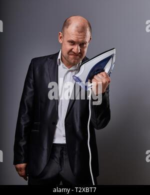 Kahlen Spaß unglücklich bedrohlichen aggressiven business Mann, der das Haus Eisen und wollen in der Klage auf grauem Hintergrund zu schlagen. Closeup Portrait - Stockfoto