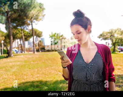 Ernsthafte junge Frau Kontrolle Handy im Freien - Stockfoto
