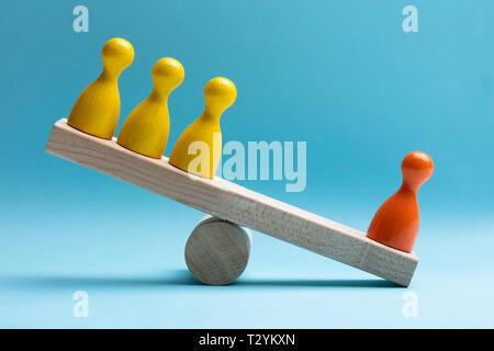 Nahaufnahme von roten und gelben Figuren Figuren Balancieren auf Holz- Wippe über blaue Fläche - Stockfoto
