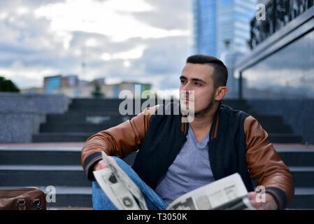 Porträt der jungen Kerl in Lederjacke lesen Zeitung in der Stadt. Der Mann sieht nachdenklich entfernt - Stockfoto