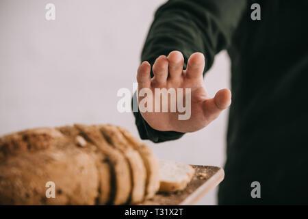 7/8-Ansicht von Mann und deutete in der Nähe von Schneidbrett mit geschnittenem Brot isoliert auf Grau - Stockfoto