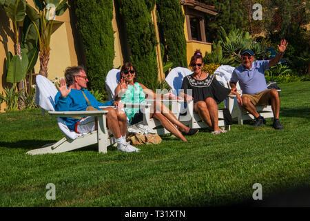 Gruppe von zwei Paare von Baby boomers Entspannung beim Sitzen auf weißen Adirondack auf luxuriösen grünen Rasen - Stockfoto